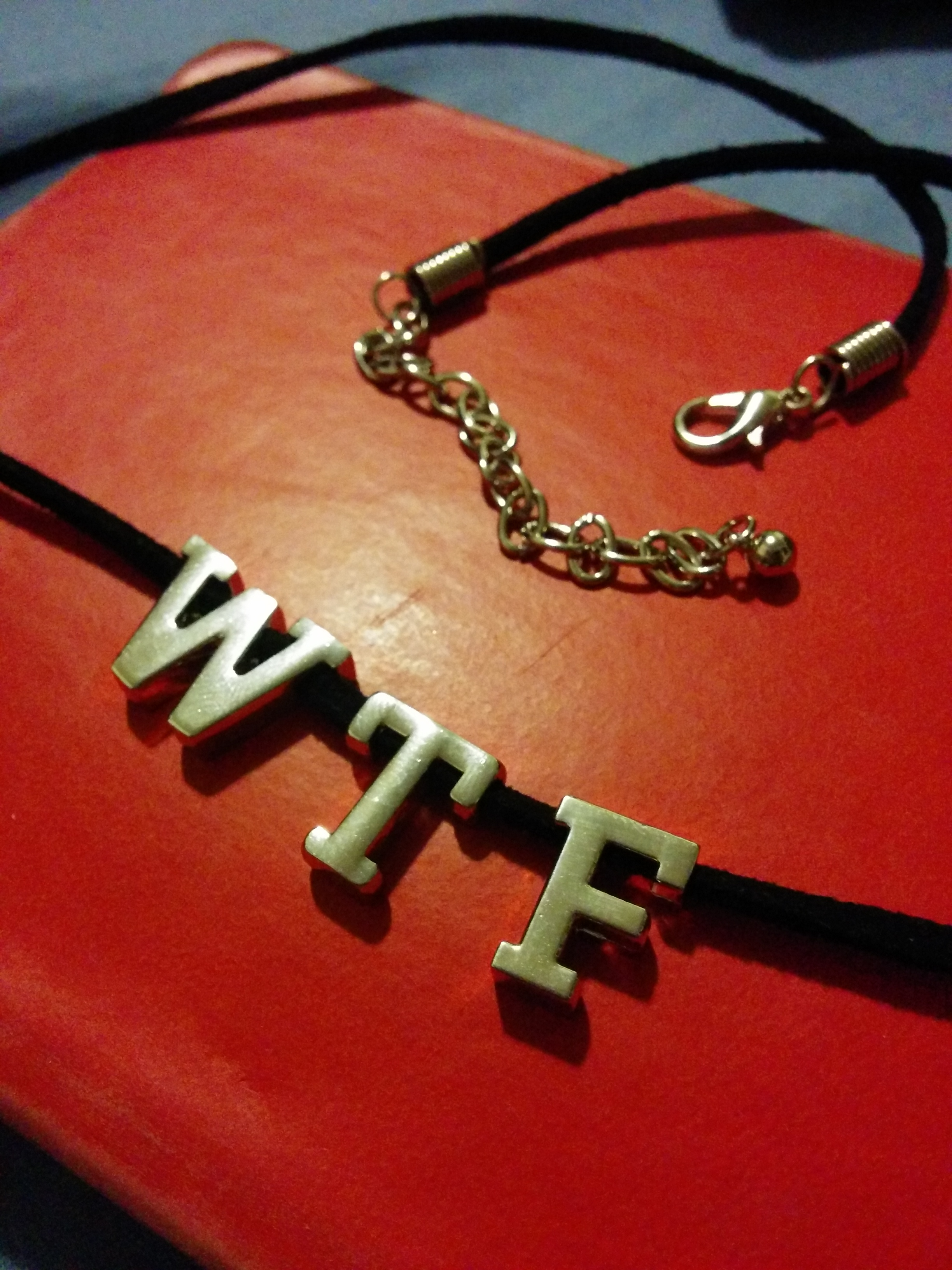 Necklace with the letters WTF on it.